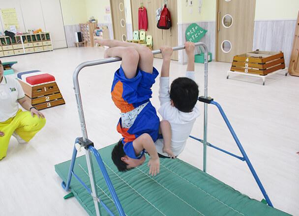 体操教室での鉄棒を使った授業のイメージ